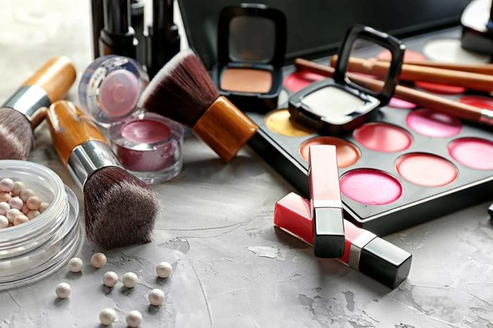 A makeup set, including blushes, lip glosses, and brushes, on a marble counter.