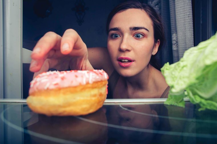 Woman reaching for donut instead of lettuce in refrigerator