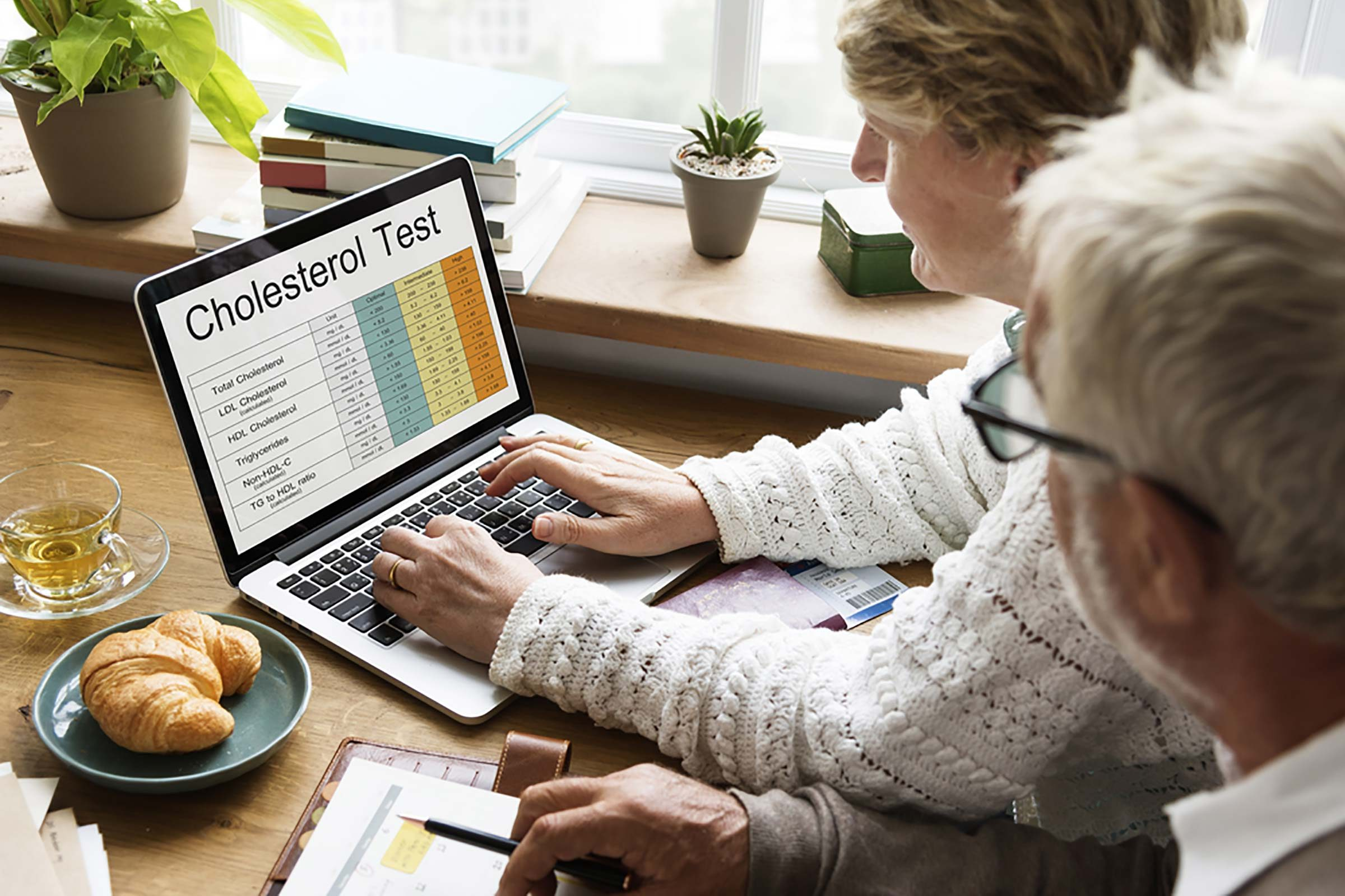 woman and man looking at cholesterol test results on a laptop