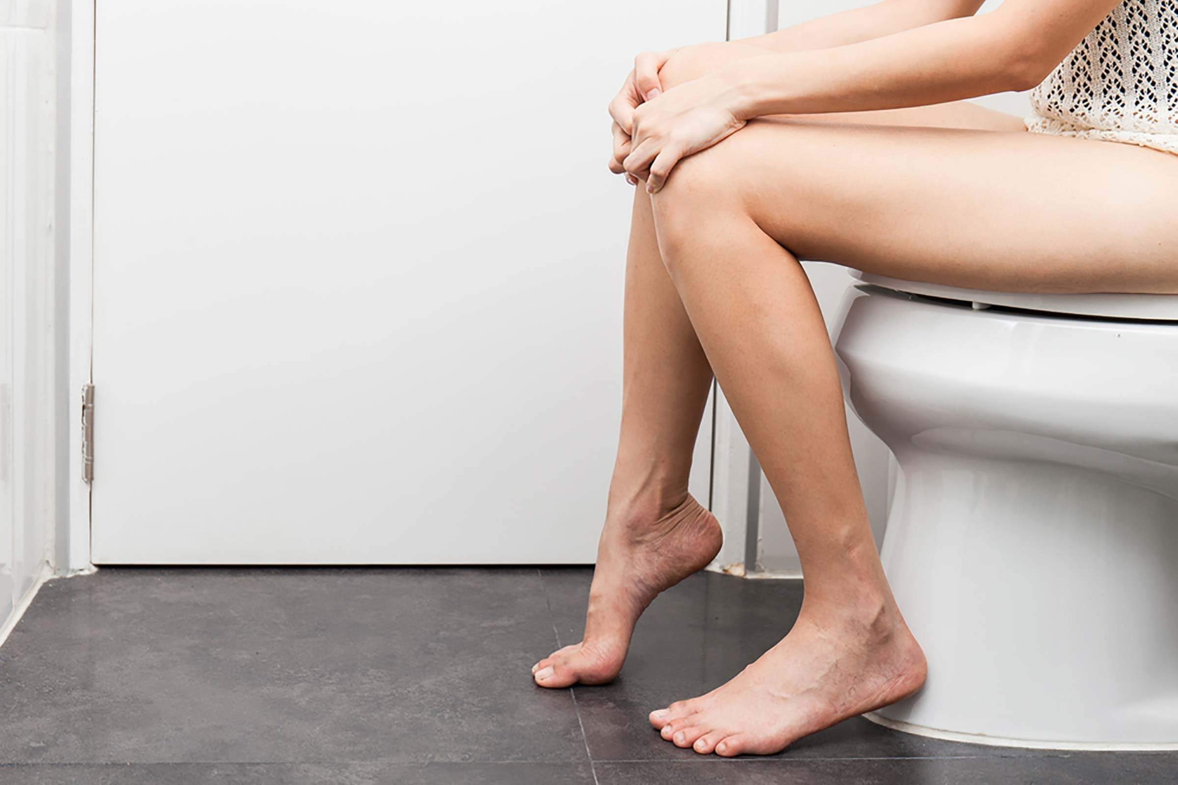 Woman sitting on a toilet in the restroom.