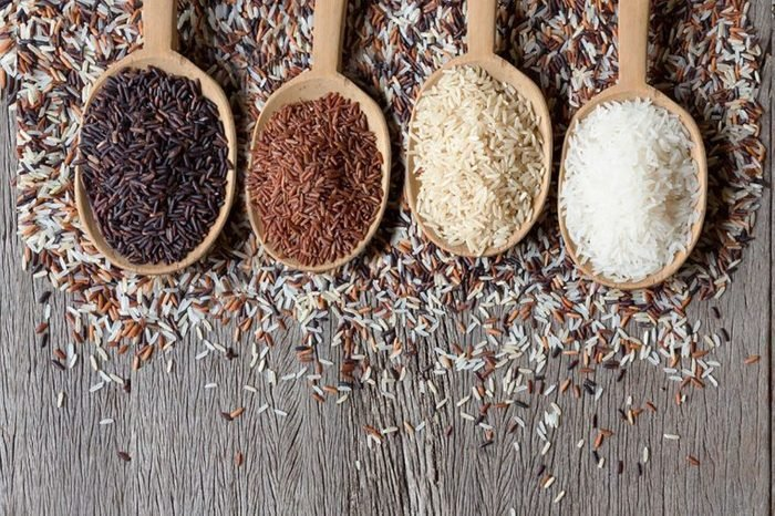 Wooden spoonfuls of black, white, brown, and red rice.