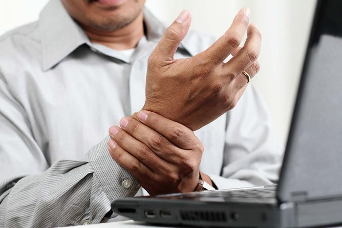 man holding his wrist in front of laptop