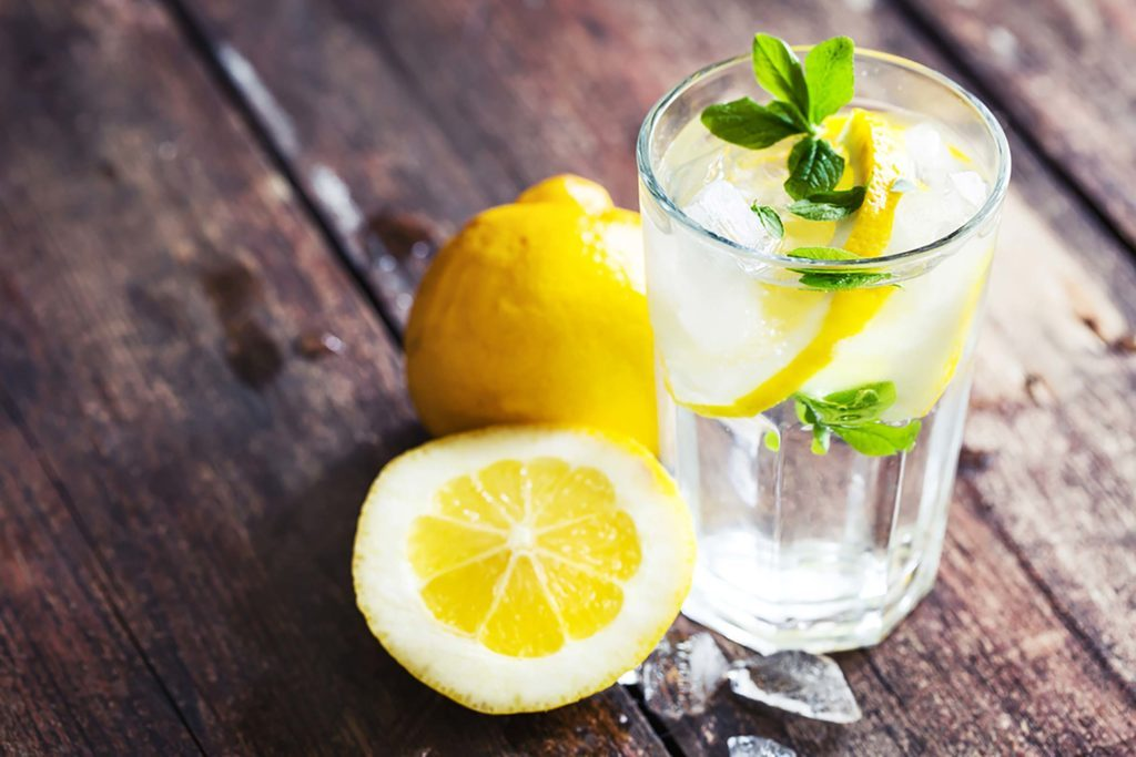 lemons on a wood table next to a glass of water with lemon slice and mint