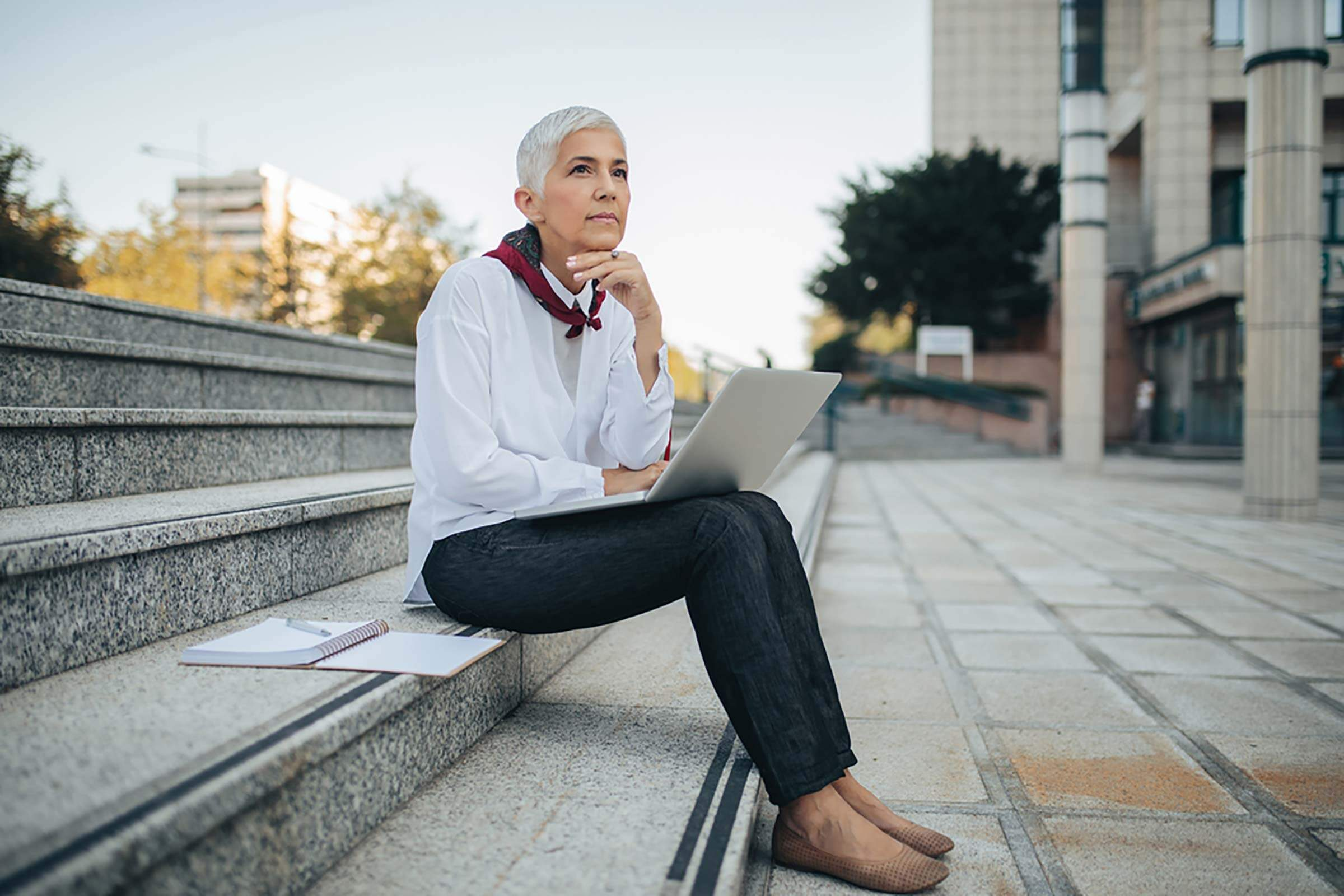 thoughtful gray-haired woman with laptop