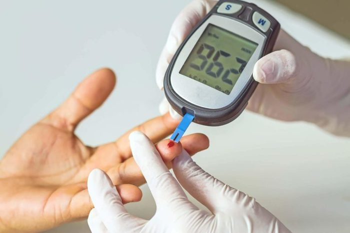 Blood pressure monitor pricking finger and showing blood glucose levels