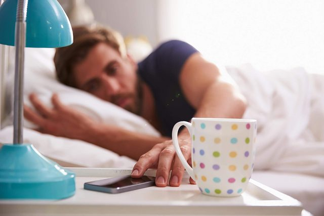 man in bed waking up and checking phone