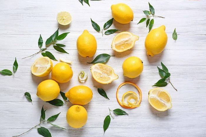artistic arrangement of whole and halved lemons with leaves