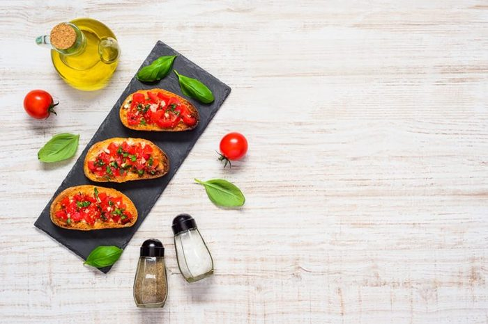 three bruschetta on a plate surrounded by tomatoes, olive oil, basil, and salt and pepper