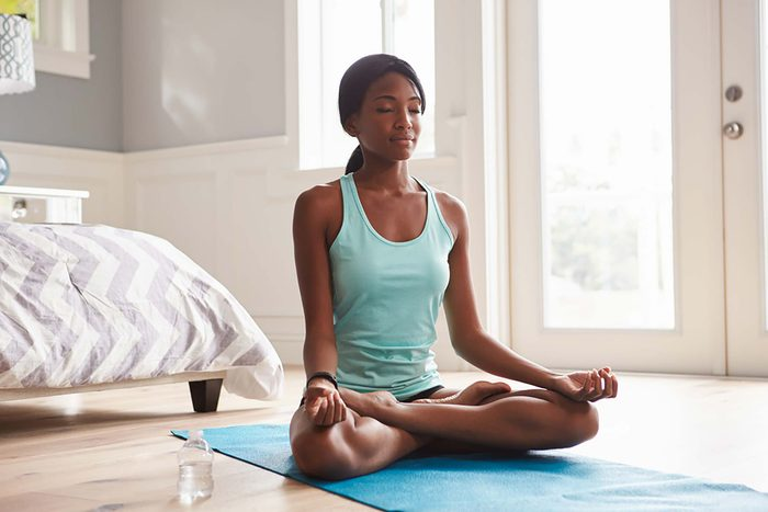Woman sitting on a yoga mat in a meditative pose.