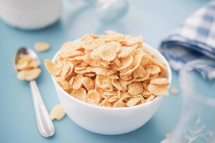Cereal flakes in a white bowl on a blue table