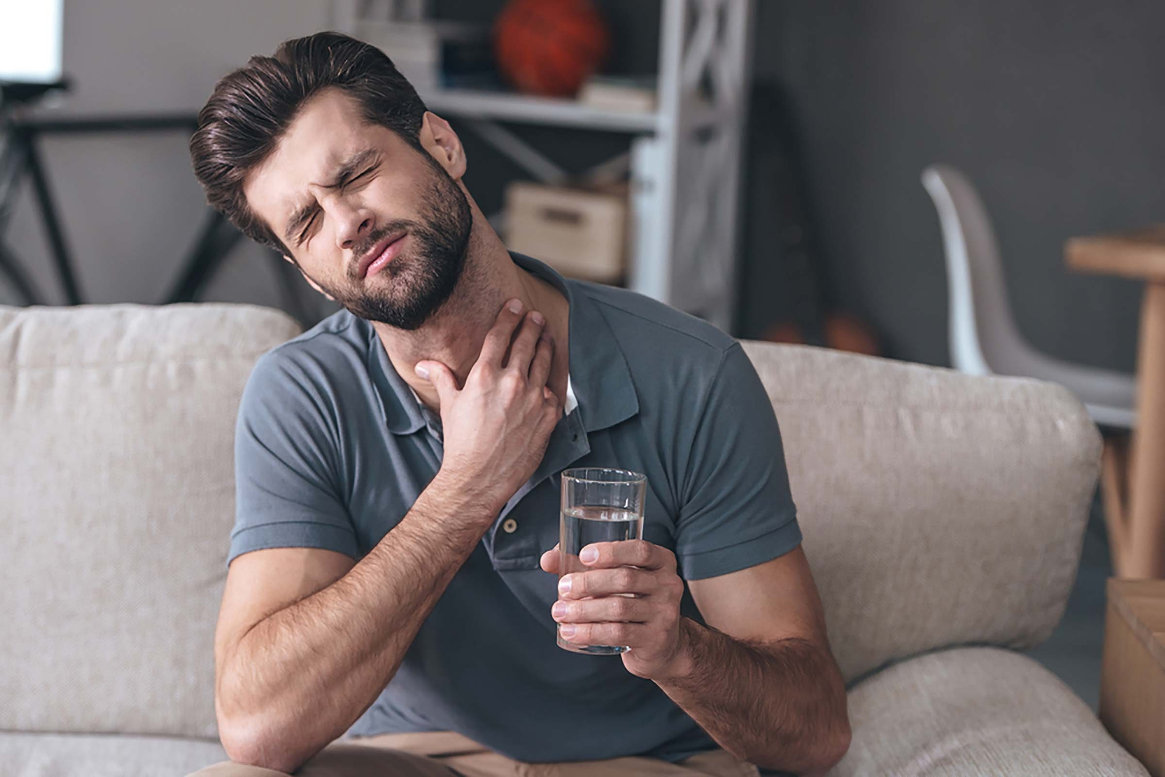 man with sore throat, holding glass of water