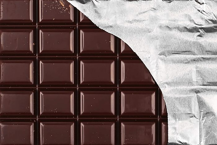 A chocolate bar half wrapped in foil