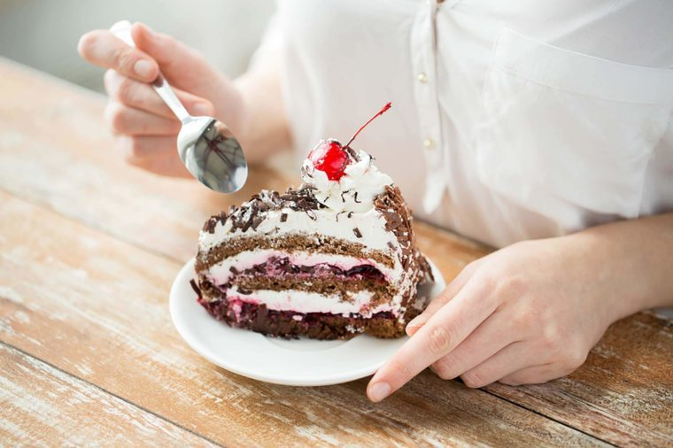 Person eating chocolate cream cake with cherry on top