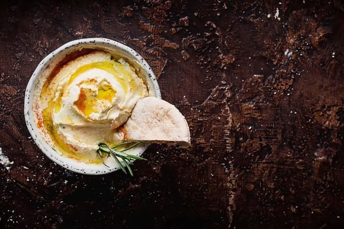 Hummus in a bowl with rosemary and pita
