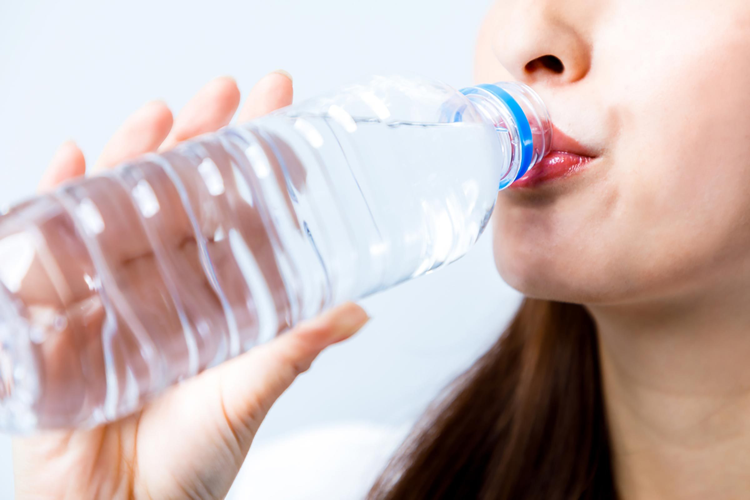 woman drinking out of a water bottle