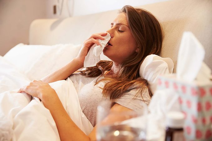 sick woman in bed with tissues