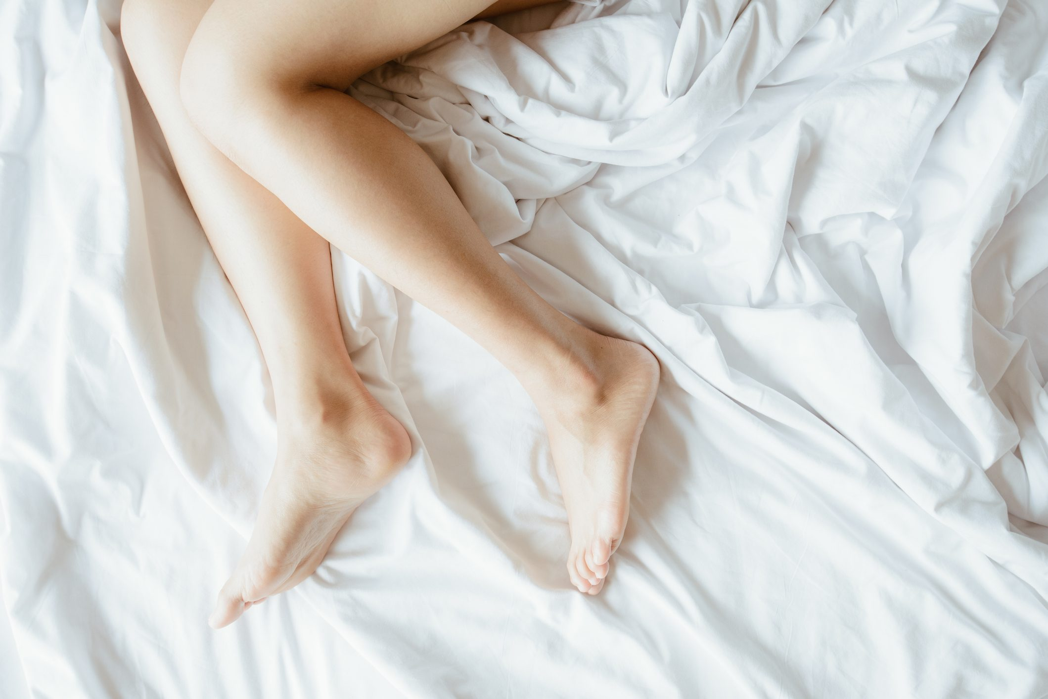 cropped shot of woman's legs in bed
