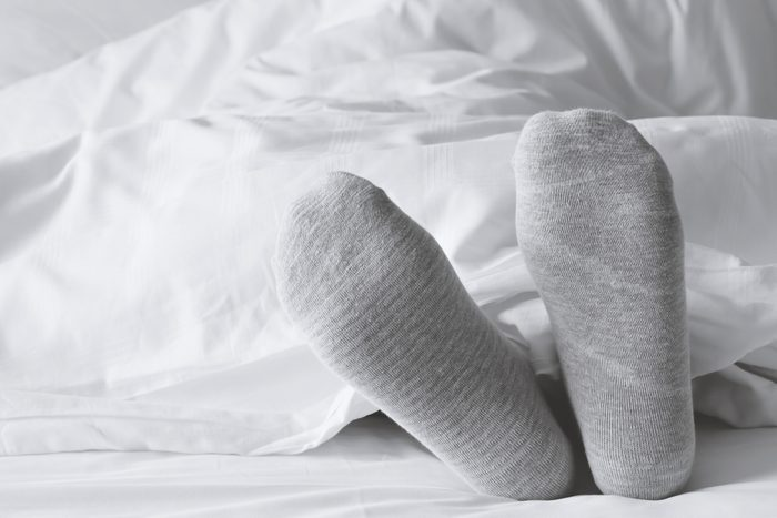 close up of gray socks on feet in white bed