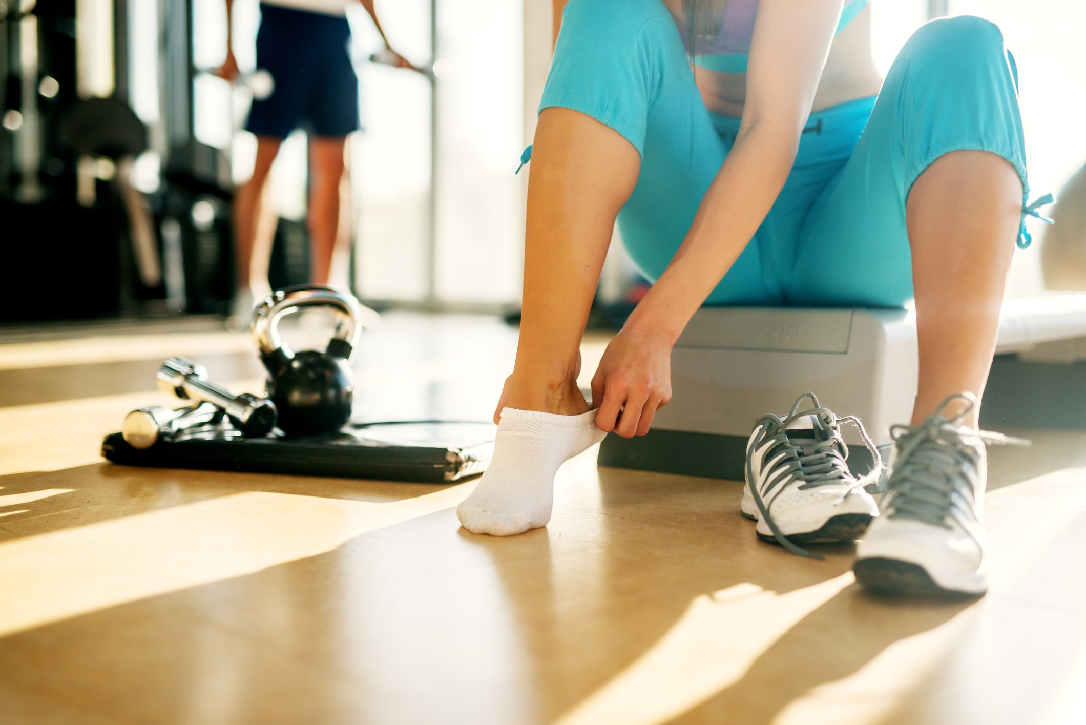 close up of young woman putting sneakers on before workout