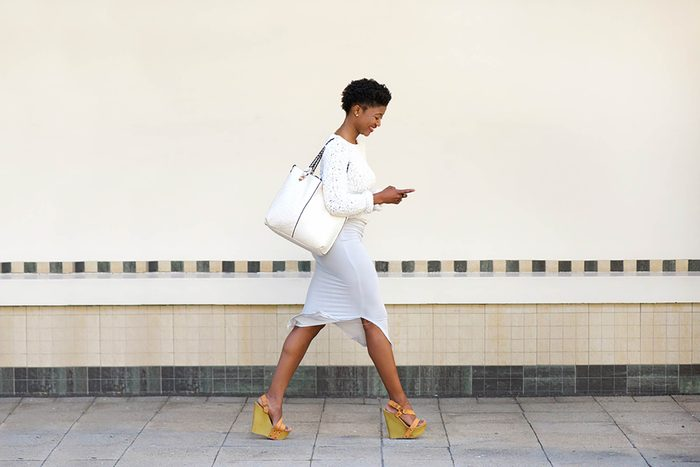woman walking and looking at phone