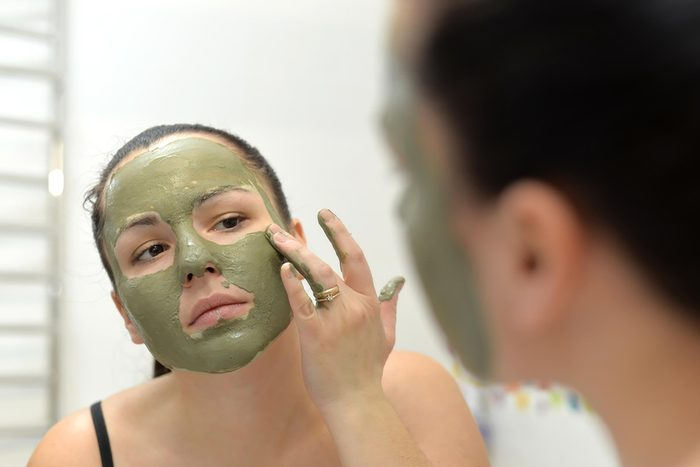Young woman applying green Bentonite-Clay mask
