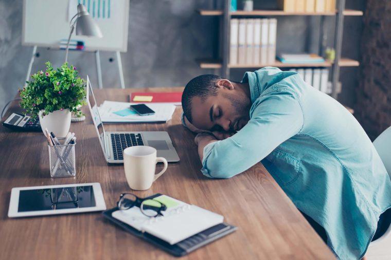 man sleeping on his desk