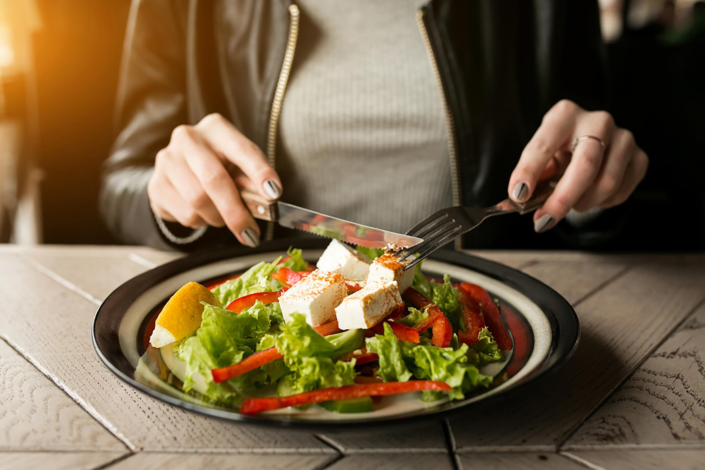 A woman eating a salad with a fork and knife at an outdoor table.