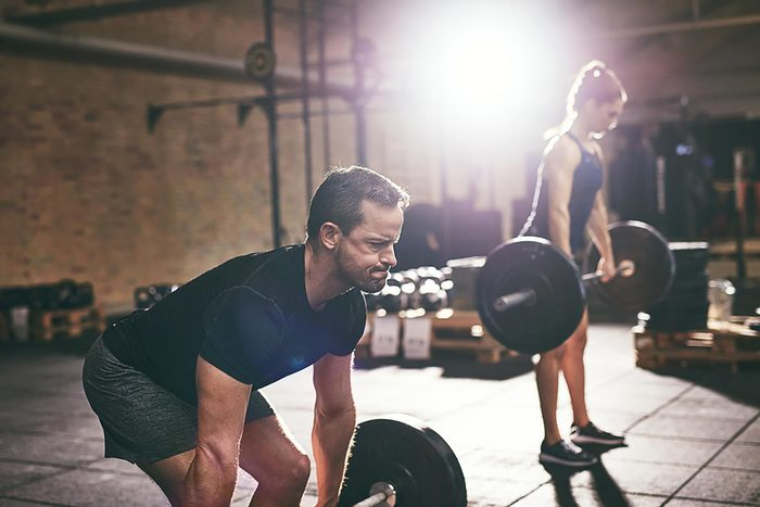 A man and woman doing barbell deadlifts in a gym.