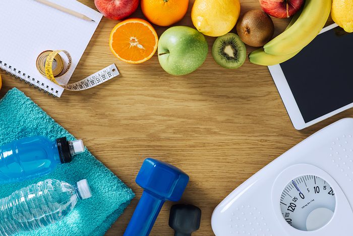Items representing health including a scale, fruit, a free weight and a water bottle