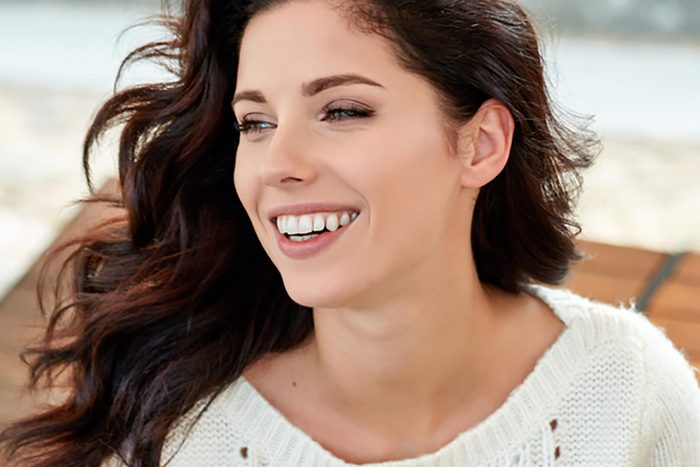 Woman with a broad, white smile.