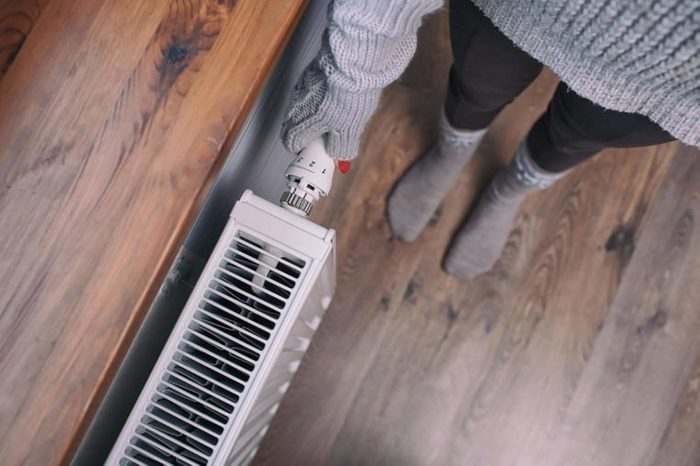 woman with gloves on adjusting a heater