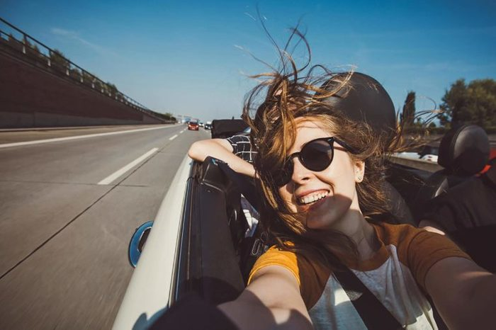 woman taking a selfie in a convertible car
