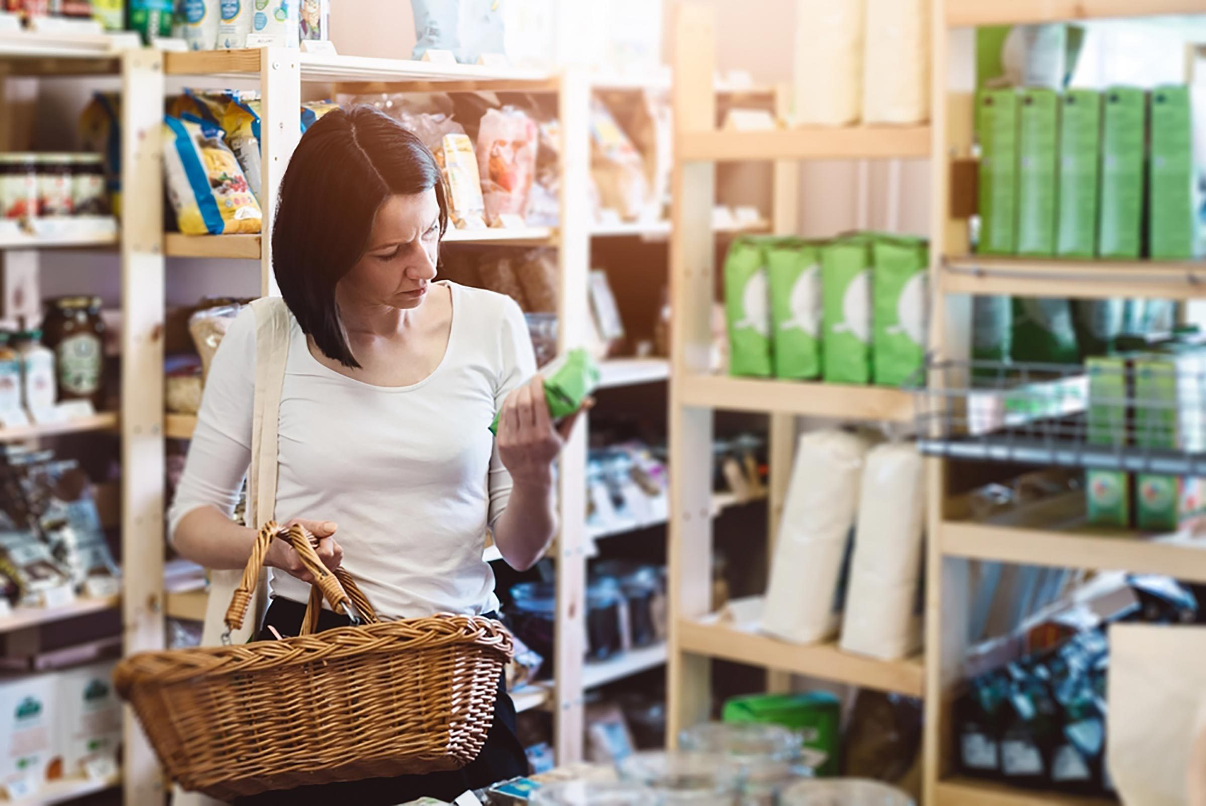 A woman carrying a basket is food shopping.