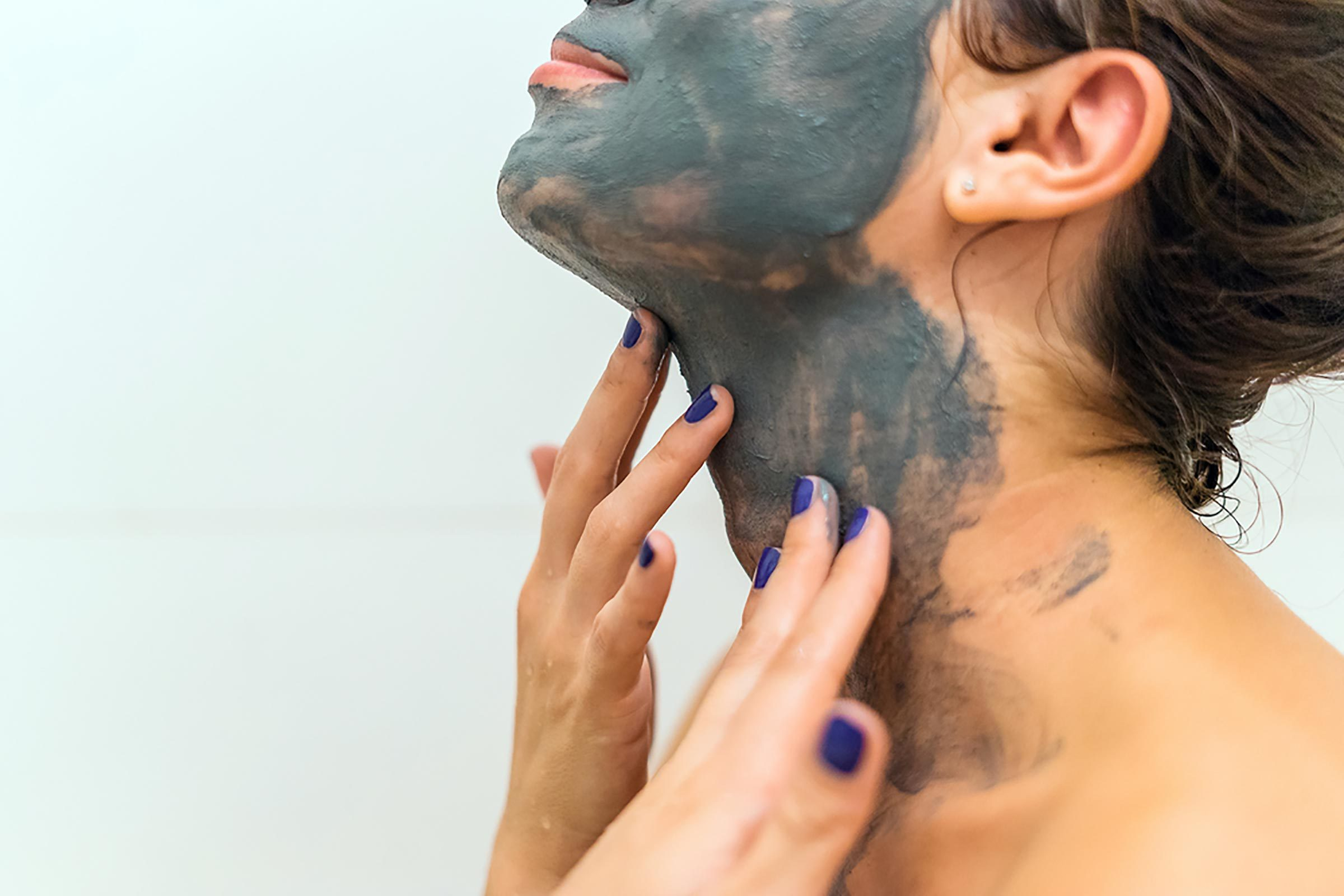 Woman applying dark green Bentonite-Clay mask