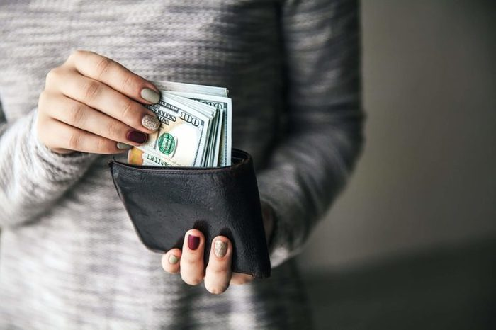 woman putting $100s into her billfold