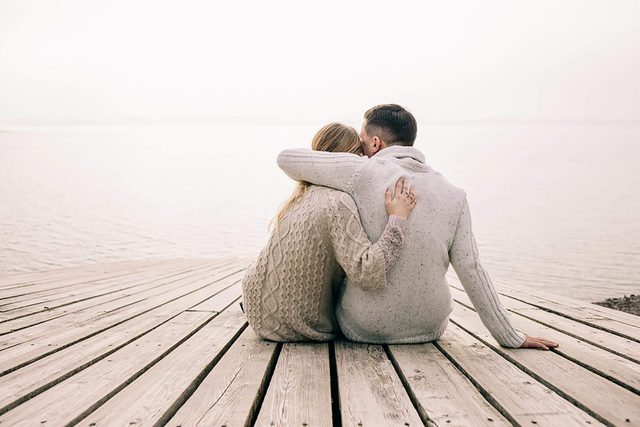 man and woman hugging on a dock