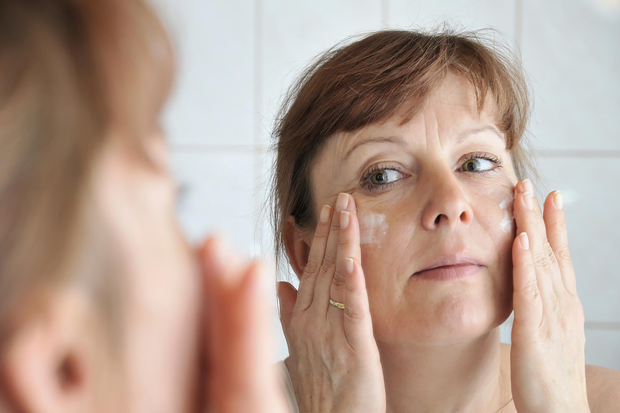 woman applying white face cream