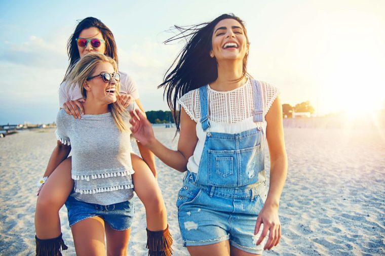 female friends laughing and walking on the beach