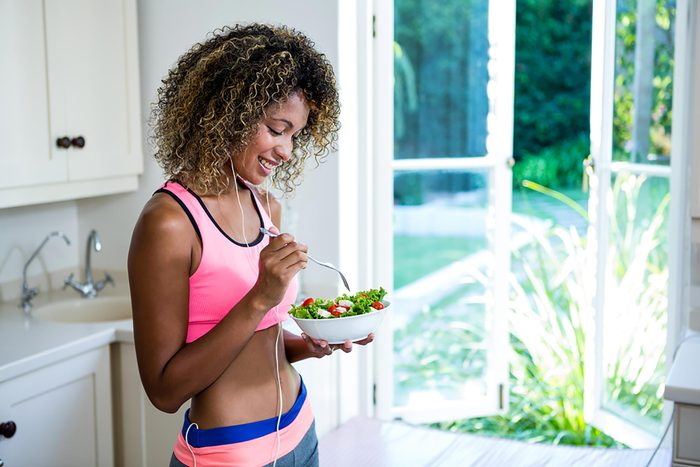 woman in fitness gear eating healthful salad