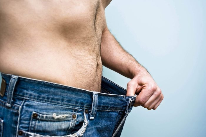 Man in jeans stretching out the loose-fitting waistband with his hand..