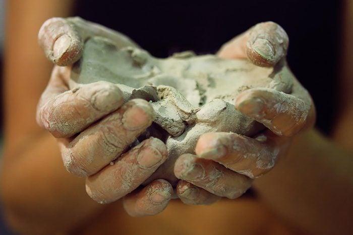 Closeup of hands cupping Bentonite-Clay