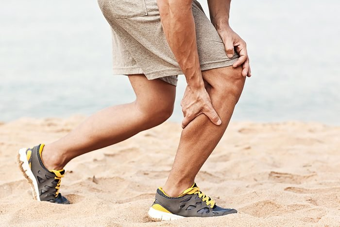 man on the beach in running shoes, grabbing his calf muscle