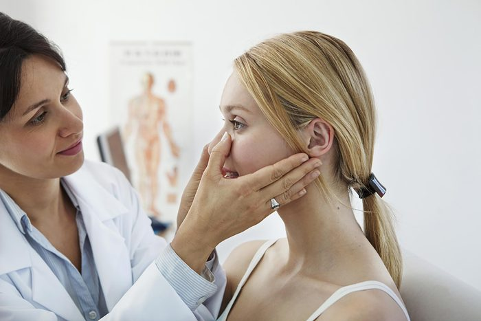 female doctor checking the sinuses of a female patient