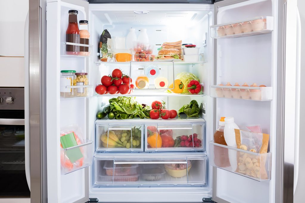 an open refrigerator filled with fruits and vegetables