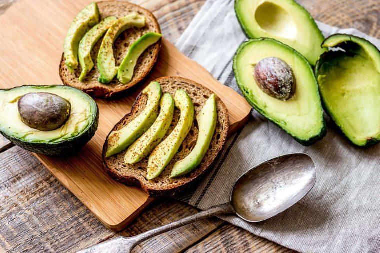 halved avocados and sliced avocado on toast