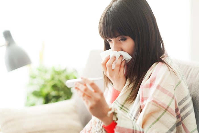 woman holding a tissue to her nose while she reads a thermometer