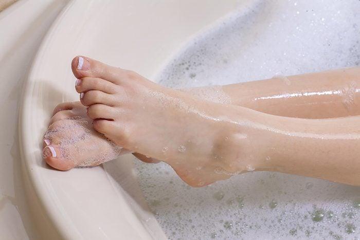 feet soaking in a soapy bathtub