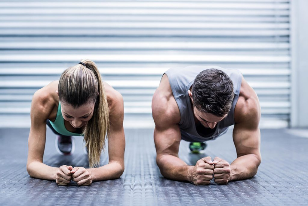 Fit man and woman holding a plank position