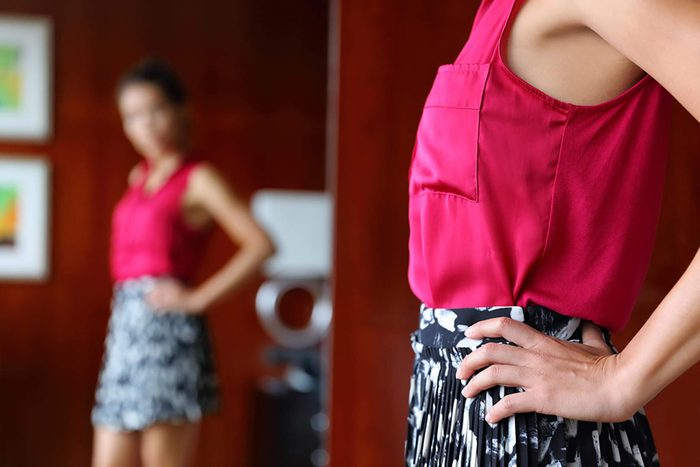 woman looking in mirror at clothes