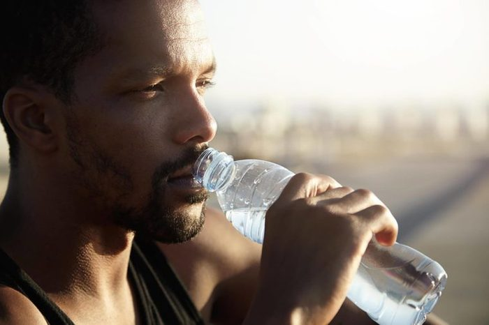 man drinking from a water bottle